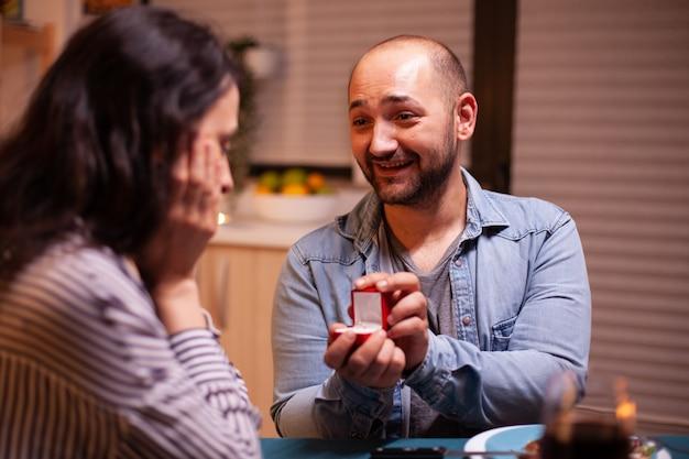 Молодой человек просит жену выйти за него замуж во время ужина на кухне. мужчина делает предложение своей девушке на кухне во время романтического ужина. счастливая кавказская женщина улыбается, будучи безмолвной