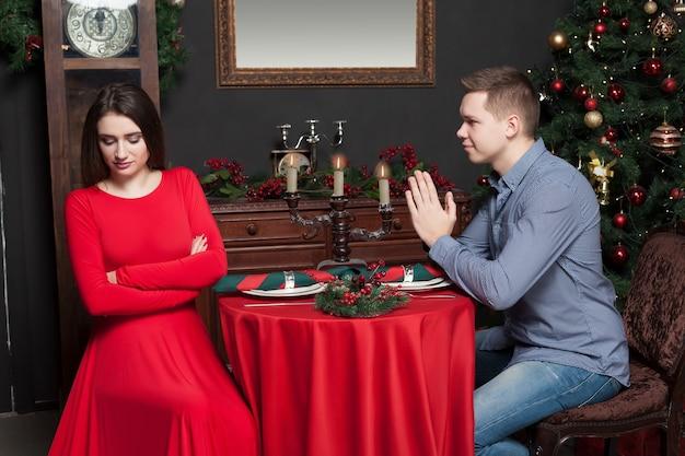 若い男は女性にチャンスを与えるように頼みます、高級レストランでカップルを愛してください。