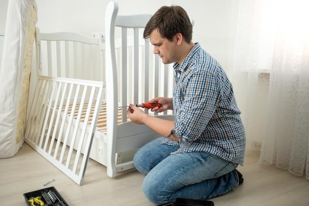 유아용 침대를 조립하는 젊은 남자
