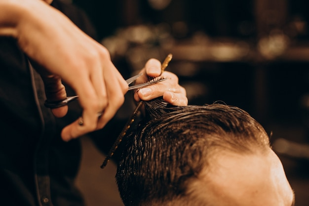 理髪店で髪をトリミングする若い男