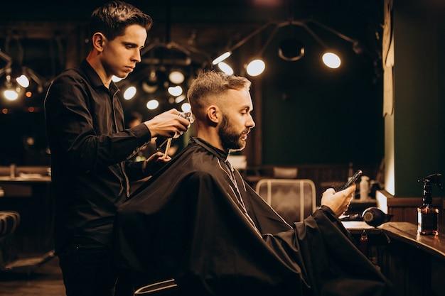 Молодой человек в парикмахерской, стригущий волосы