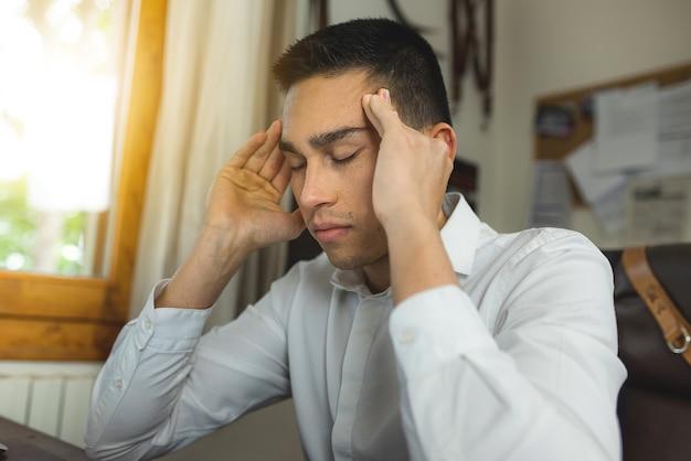 노트북 컴퓨터 책상에서 젊은 남자는 두통 때문에 작동을 중지합니다. 향하는 손과 닫힌 눈으로.