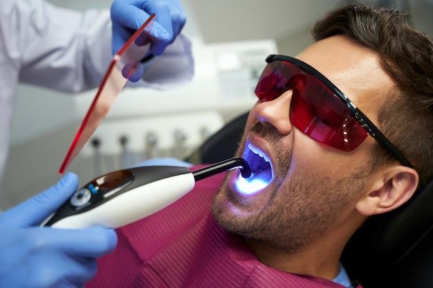 Молодой человек на приеме у стоматолога, лечится синим светом