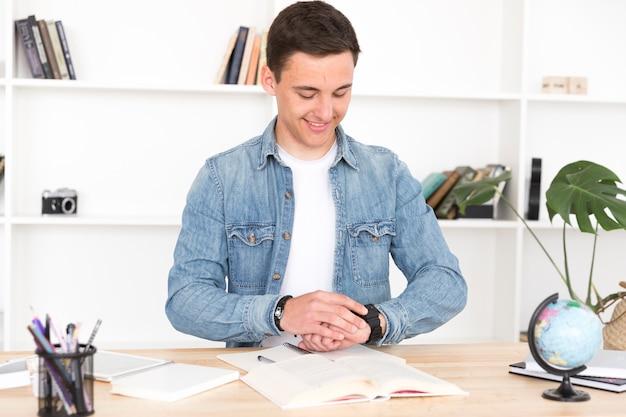 Молодой человек за столом смотрит на часы