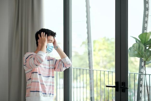 집에 있는 젊은 남자는 창 흰색 배경 근처에 의료 마스크를 쓰고 검역소에 있습니다. 코로나바이러스, 질병, 감염, 검역, 수술용 붕대, 의료용 마스크, 우울증