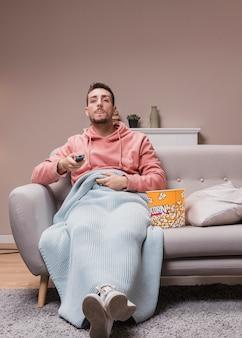 Молодой человек дома смотрит телевизор