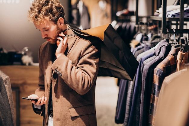 Молодой человек в магазине мужской одежды разговаривает по телефону