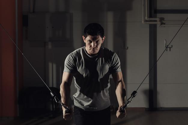 ジムの若い男は、胸筋、クロスオーバーの手の減少で運動します。調色、ハードライト。