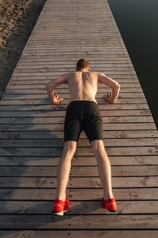 Young man athlete doing push-ups outdoors