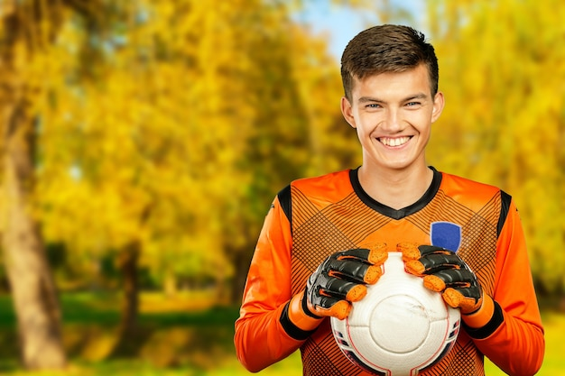 Young man athlete football soccer player. outdoors park, sunny autumn day