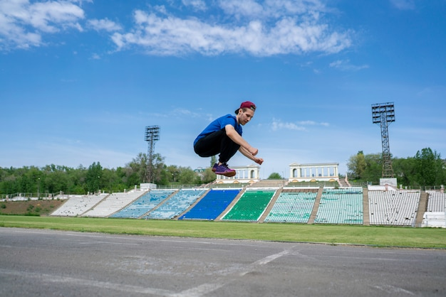 Young man athlete practice high jump fly in the air at the stadium on a summer days