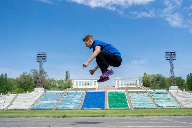 Молодой человек спортсмен тренируется в прыжках в высоту, летит в воздухе на стадионе в летние дни