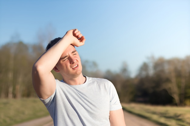Young man athlete received sun and heat stroke and headache. guy holds his head with his hands and protects himself from the sun in outdoors.