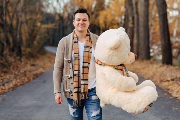 Young man at autumn park road with big bear toy