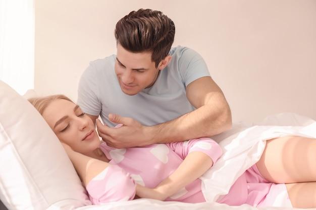 집에서 침대에서 아름다운 그의 여자 친구를 깨우는 젊은 남자