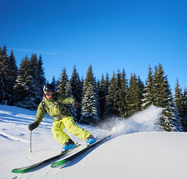 Молодой человек, путешествующий на лыжах вверх и вниз по склонам. тренировка мужского лыжника в солнечный зимний день. концепция катания на горных лыжах.