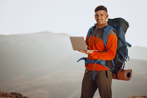 Young man backpacker using his laptop in mountain journey