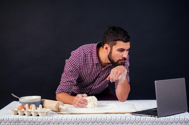 Пекарь молодой человек готовит хлеб, макароны, пиццу, глядя на ноутбук, сидя за столом в студии на черном фоне copyspace.