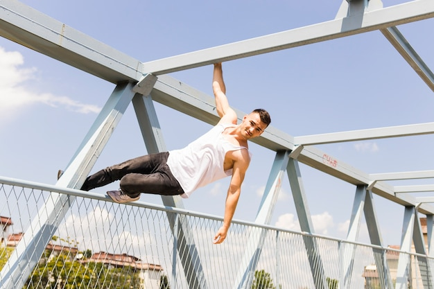Young man balancing on the railing of a bridge