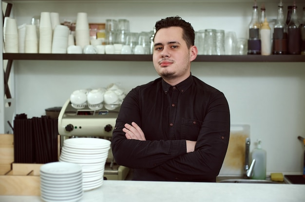 Young man barista in a working environment behind the bar