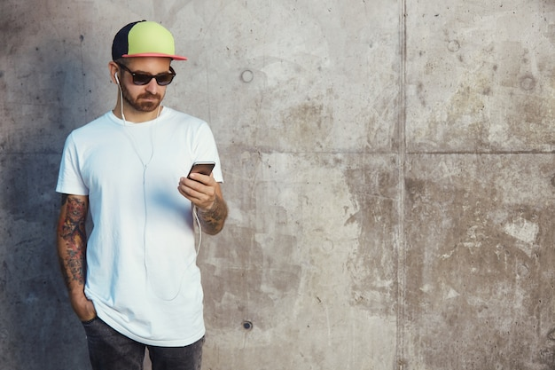 Young man in baseball cap, sunglasses and white blank t-shirt reading something on his smartphone standing next to a gray concrete wall