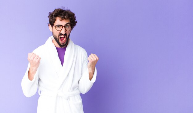 Young man in a bathrobe shouting aggressively with an angry expression and with fists clenched
