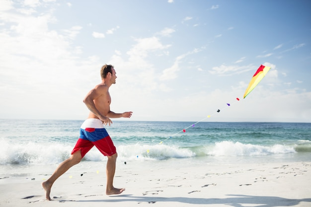 Young man on beach playing with a kite