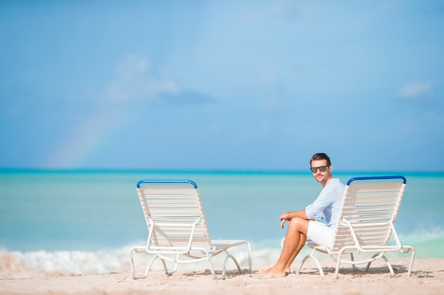 Young man on the beach rest on the chaise-lounge alone