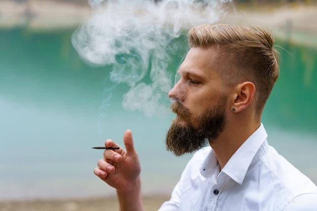 젊은 남자 수염은 담배를 피우거나 담배 남자는 담배에 중독되어 항상 많은 양의 담배를 피웁니다.