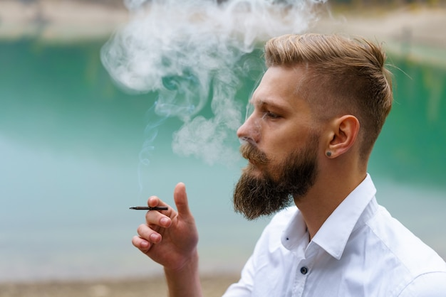 Young man beard smokes cigarette or tobacco guy is addicted to cigarettes and always smokes lot of t...