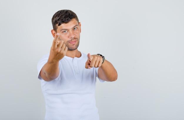 Giovane che fa cenno e punta il dito alla telecamera in t-shirt bianca e sembra positivo, vista frontale.