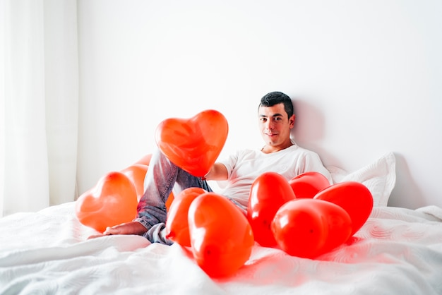 Young man on bed between balloons in form of hearts