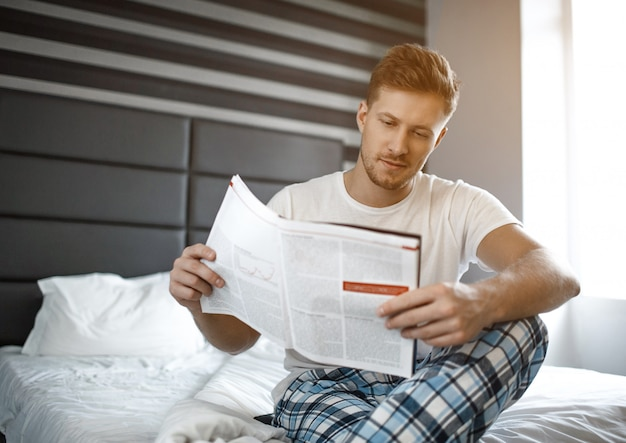 Young man on bed early morning. he sit and read journal. small smile on face. concentrated.