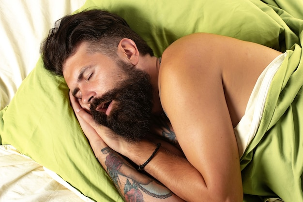 Young man in bed - trying to sleep. handsome man sleeps in the bedroom - lying on bed.