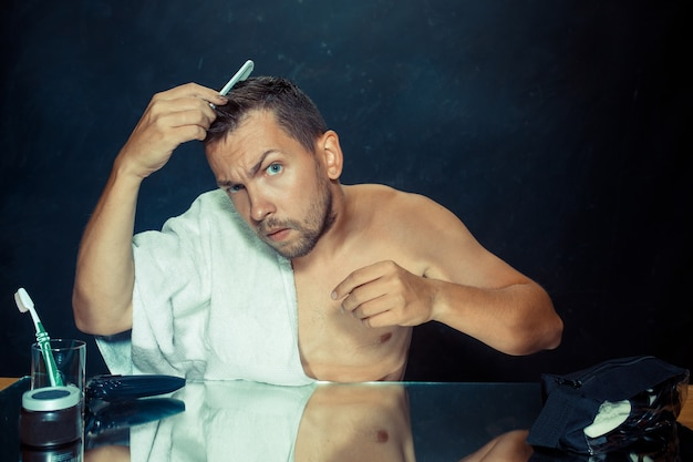 Il giovane in camera da letto seduto davanti allo specchio a grattarsi la barba a casa. concetto di emozioni umane e problemi con i capelli