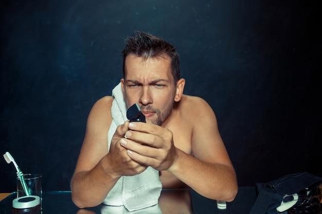 Il giovane in camera da letto seduto davanti allo specchio a grattarsi la barba a casa. concetto di emozioni umane
