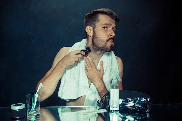 The young man in bedroom sitting in front of the mirror scratching his beard at home. human emotions concept