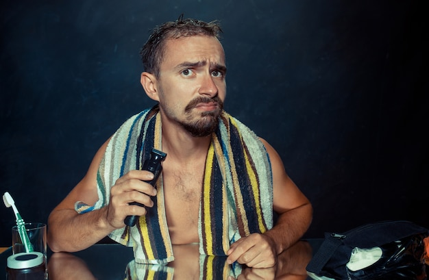 Il giovane in camera da letto seduto davanti allo specchio a grattarsi la barba a casa. le emozioni umane e il concetto di stile di vita