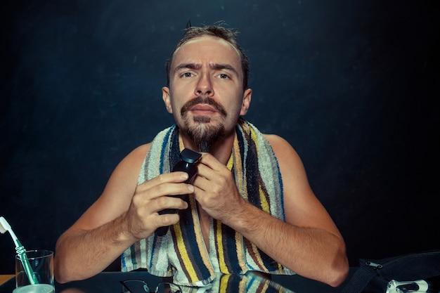 Giovane uomo in camera da letto seduto davanti allo specchio grattandosi la barba a casa