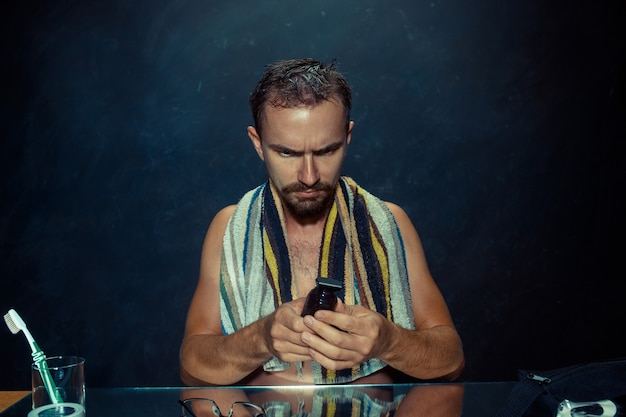 The young man in bedroom sitting in front of the mirror scratching his beard at home