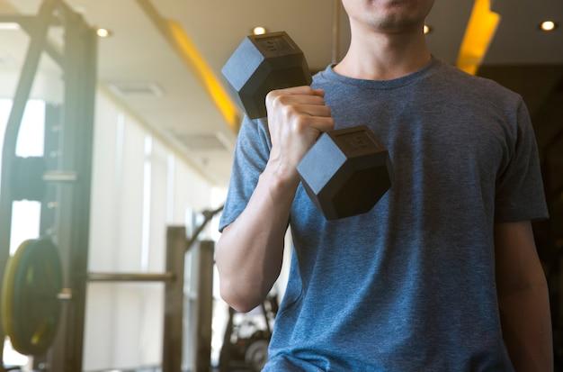 Young man beginner exercising with dumbbell flexing muscles at gym, sport training concept