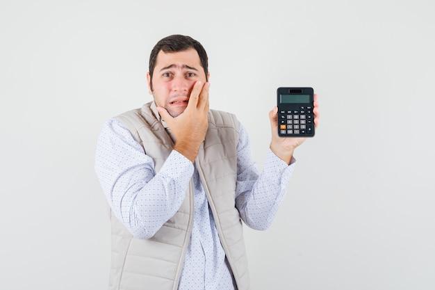Giovane uomo in giacca beige e berretto che tiene la calcolatrice in una mano mentre copre parte del viso con la mano e sembra sorpreso, vista frontale.