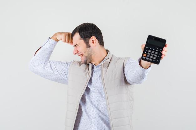 Giovane uomo in giacca beige e berretto che tiene la calcolatrice in una mano mentre mette la mano sulla testa e sembra tormentata, vista frontale.