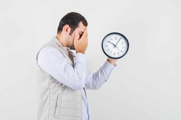 Giovane uomo in giacca beige e berretto tenendo l'orologio in uno e coprendo gli occhi con la mano e guardando esausto, vista frontale.