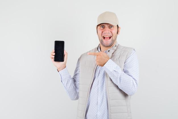 Giovane uomo in giacca beige e berretto tenendo il telefono in una mano e indicandolo e guardando felice, vista frontale.