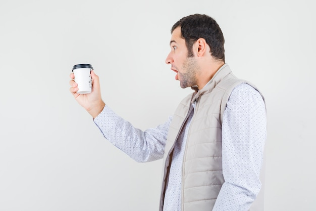 Young man in beige jacket holding takeaway cup of coffee and looking at it and looking surprised , front view.