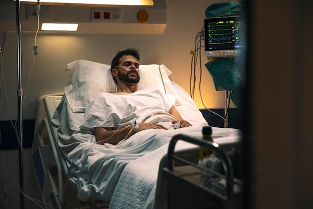 Giovane malato in un letto d'ospedale Foto Gratuite