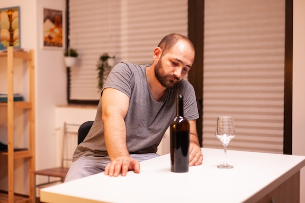 Young man being lonely in home having alcohol addiction sitting at table in kichen. unhappy person disease and anxiety feeling exhausted with having alcoholism problems.