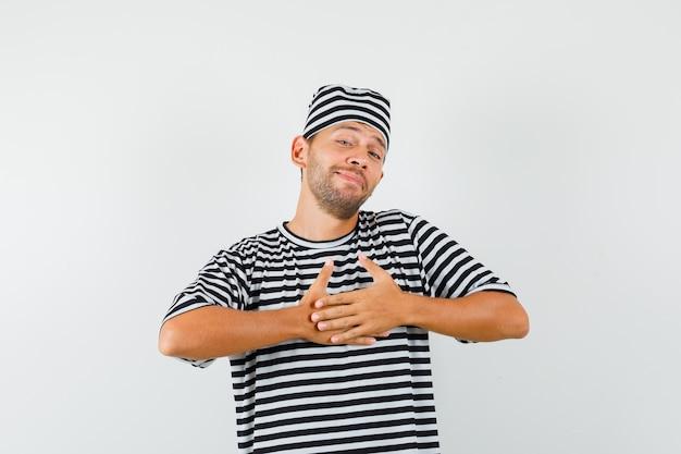 縞模様のtシャツの帽子の贈り物や褒め言葉に満足し、感謝している若い男