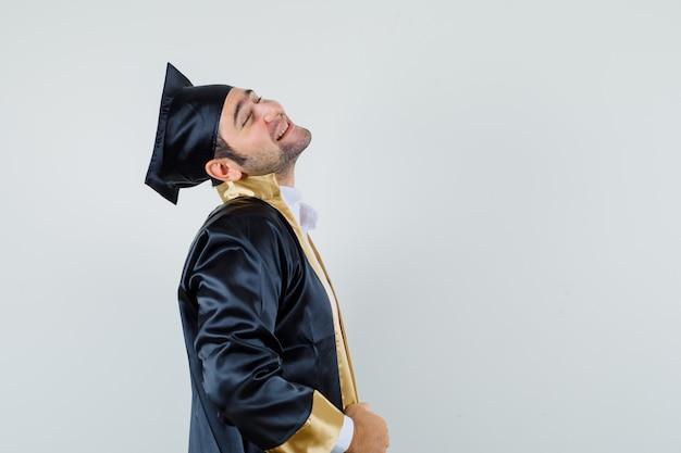 Giovane che piega la testa indietro in uniforme laureato e sembra tranquillo.
